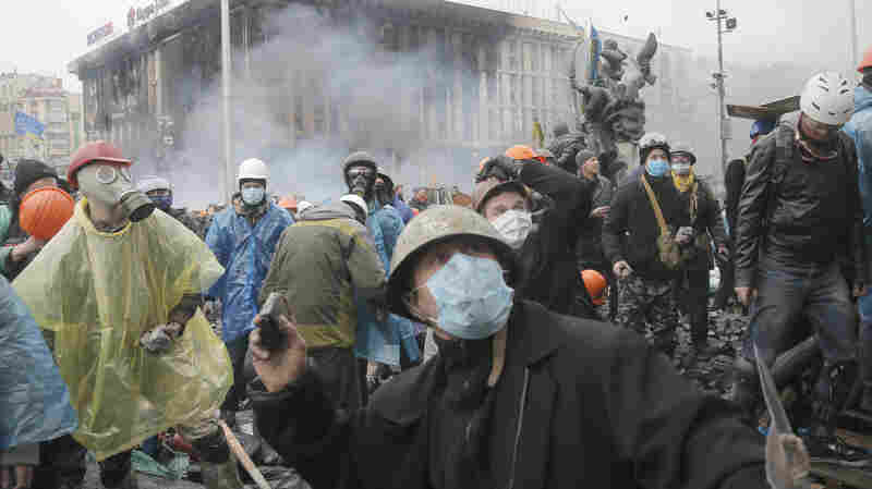 Anti-government protesters throw stones during clashes with riot police in Kiev's Independence Square, the epicenter of the Ukraine's current unrest, on Wednesday. The deadly clashes have drawn sharp reactions from Washington and generated talk of possible European Union sanctions.