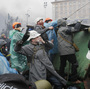 Anti-government protesters throw stones during clashes with riot police in Kiev's Independence Square on Wednesday.