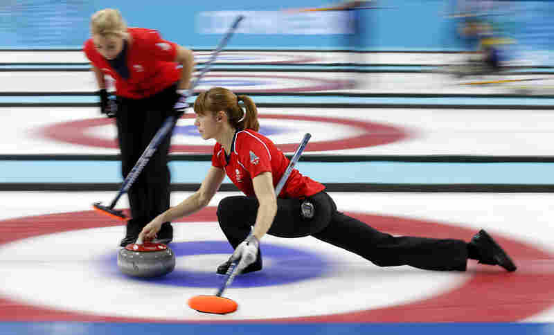 Britain's Claire Hamilton delivers the rock while her teammate Anna Sloan prepares to sweep during the women's curling semifinal game against Canada during the Sochi Winter Olympics on Wednesday. Canada won 6-4.