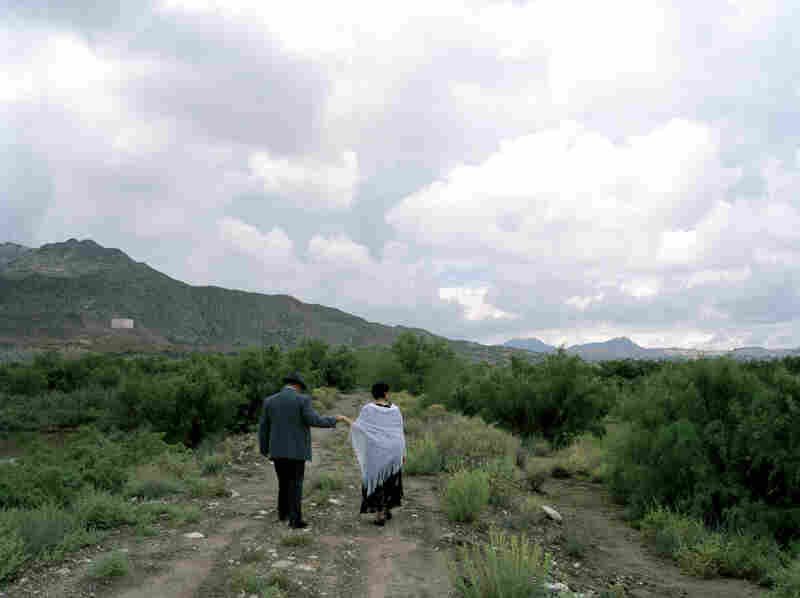 Mr. and Mrs. Ysidro Chavez walk in Sunland Park, N.M. Beyond them is Mt. Cristo Rey, where New Mexico, Texas and Chihuahua, Mexico, meet.
