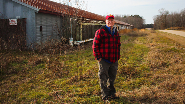 Benny Bunting, a farm advocate for Rural Advancement Foundation International-USA, in front of one of his old chicken houses in Oak City, N.C. (NPR)