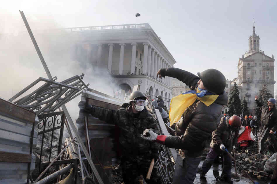 An anti-government protester throws a stone during clashes in Kiev. At least 26 people were killed Tuesday and an additional 241 were injured on Tuesday, according to The Associated Press.