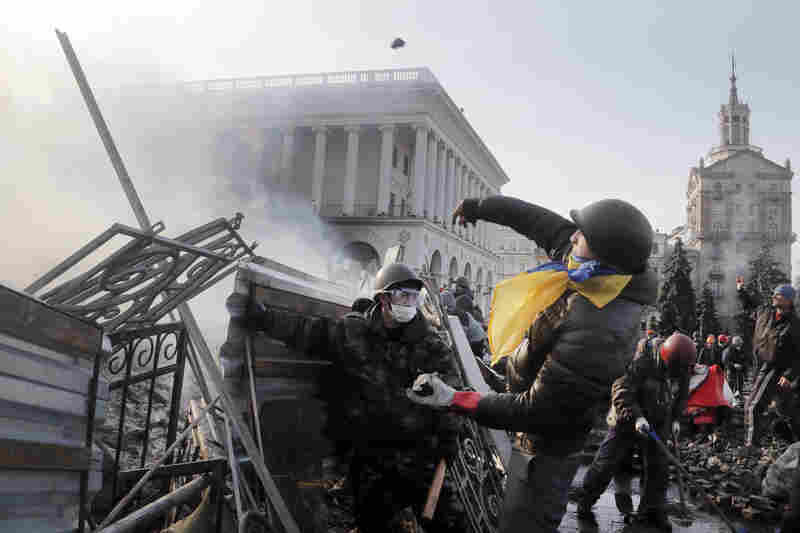 An anti-government protester throws a stone during clashes with riot police Wednesday in Kiev. Streets and squares in Ukraine's capital are littered with rocks, bricks, spent stun grenades and tear gas canisters, rubber bullets and burning tires, the BBC's David Stern said on Morning Edition.