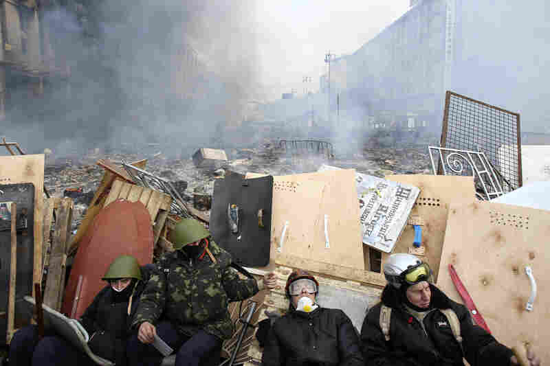 Anti-government demonstrators rest at a barricade near the site of clashes with Interior Ministry members and riot police in Kiev.