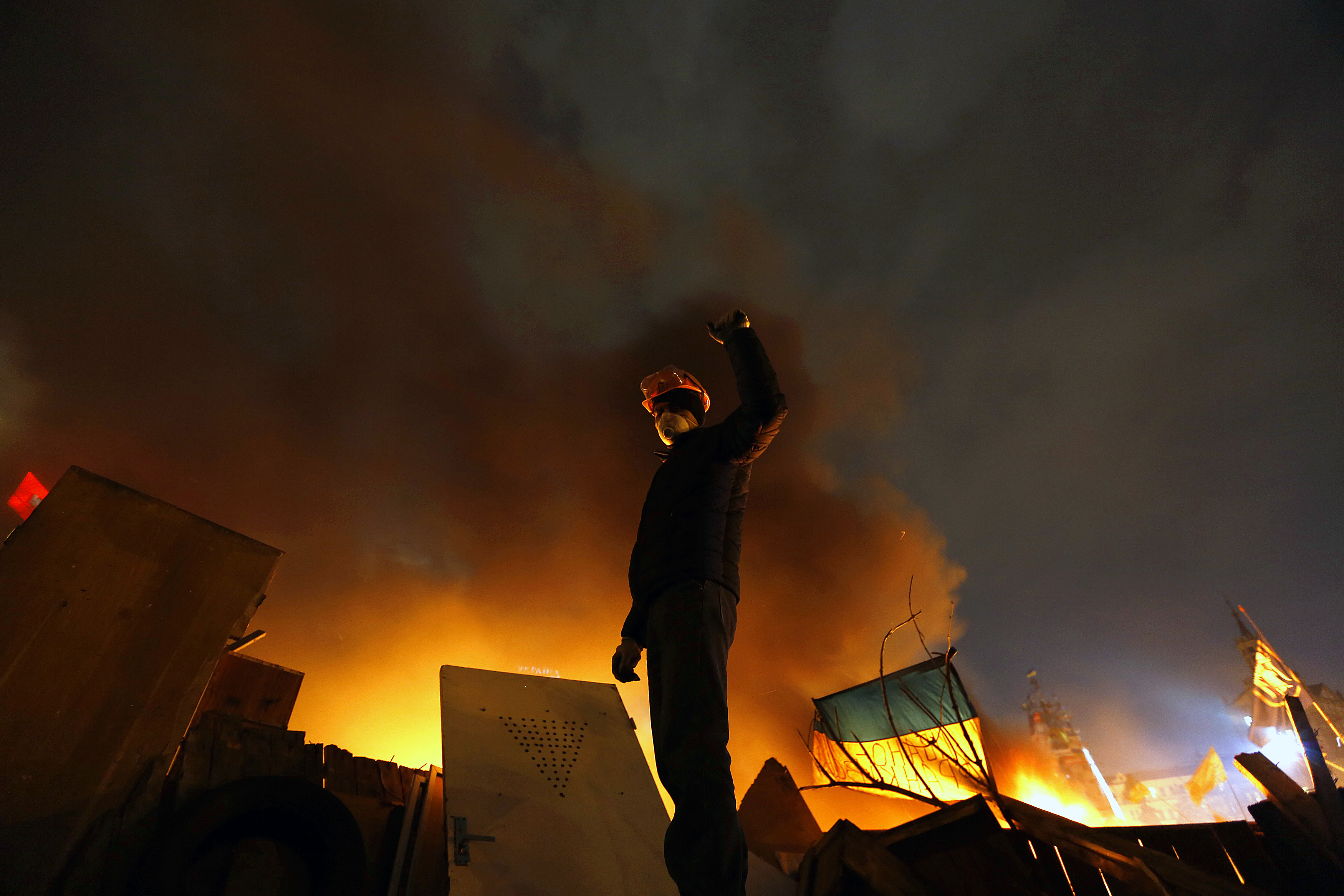 An anti-government protester stands behind burning barricades in Kiev's Independence Square on Tuesday. The international community on Wednesday urged restraint and threatened sanctions against those responsible for the violence.