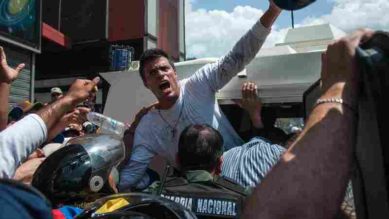 Venezuelan opposition leader Leopoldo Lopez (in white shirt) as he turned himself over to police on Tuesday in Caracas.