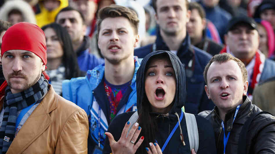 Russian fans who gathered in Sochi's Olympic Park react with dismay as they watch a broadcast of the ice hockey match between Russia and Finland.