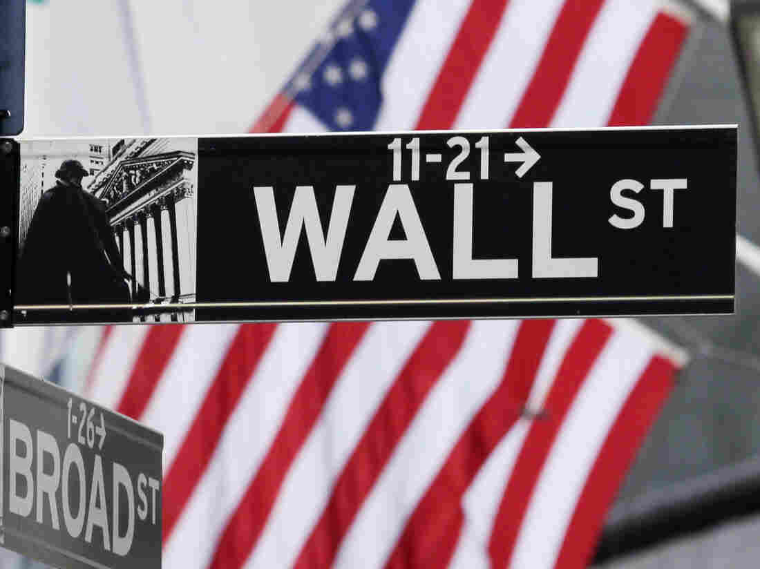 The American Flag can be seen behind a sign for Wall Street near the New York Stock Exchange in New York City on March 5, 2013.