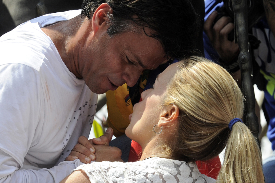 Leopoldo López, an ardent opponent of Venezuela's socialist government facing an arrest warrant after President Nicolas Maduro ordered his arrest on charges of homicide and inciting violence, kisses his wife Lilian Tintori, before turning himself in to authorities on Tuesday. (Leo Ramirez/AFP/Getty Images)