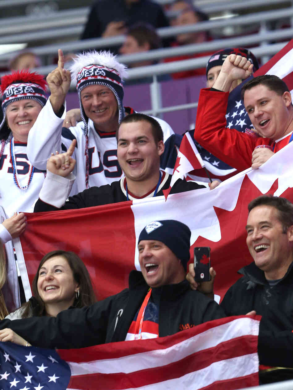 U.S. and Canadian fans attend the women's hockey gold medal game in Sochi Thursday. A recent Gallup poll finds that Americans see Canada in the most favorable light, compared to other countries.