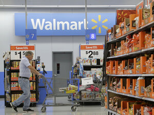 A man shops at a Wal-Mart store in San Jose, Calif., in September. Wal-Mart on Thursday reported that its annual profits fell.