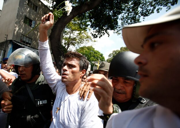 Opposition leader Leopoldo Lopez is flanked by Bolivarian National Guards after Lopez surrendered in Caracas, Venezuela on Tuesday.