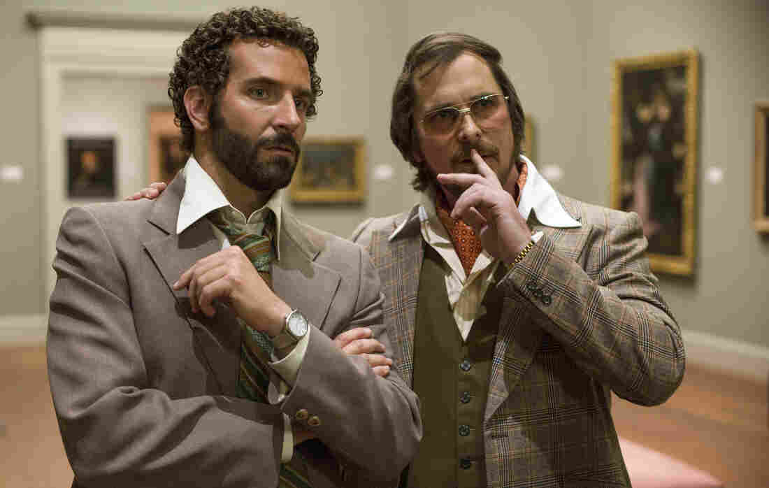 A '70s con artist (Christian Bale, right) is forced to team up with an FBI agent (Bradley Cooper, left) in American Hustle, inspired by a real-life sting targeting corrupt politicians.