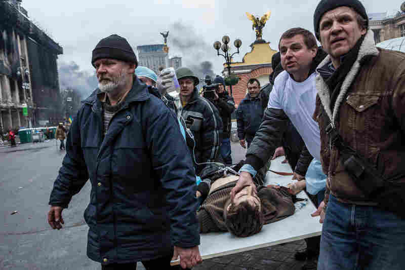 People carry a wounded anti-government protester to a waiting ambulance in Kiev. The international community on Wednesday urged restraint and threatened sanctions against those responsible for the violence.