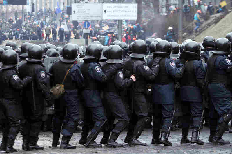 Riot police face anti-government protesters during clashes in Kiev. Police there attacked an opposition camp at the center of the massive anti-government protests that began in November.