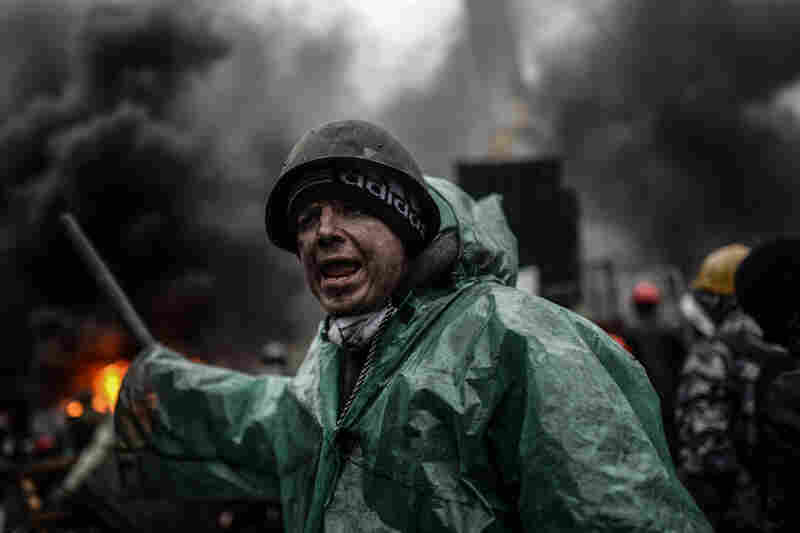"A protester stands behind barricades during clashes with police in Kiev. NPR's Soraya Sarhaddi Nelson reported on Morning Edition that it's ""absolute chaos"" in the area."