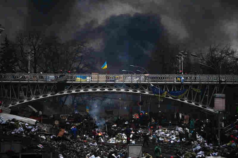 """Night falls as anti-government protesters rebuild barricades following continued clashes with police in Independence Square in Kiev. """"Interior ministry says 67 police captured by protesters in Kiev,"""" the AP reports."""