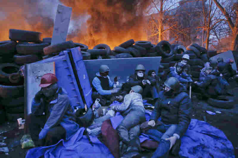 """Protesters rest near burning barricades in Kiev. The protesters say police forces and """"thugs"""" who support President Viktor Yanukovych never observed the truce that was announced Wednesday night, according to NPR's Soraya Sarhaddi Nelson."""