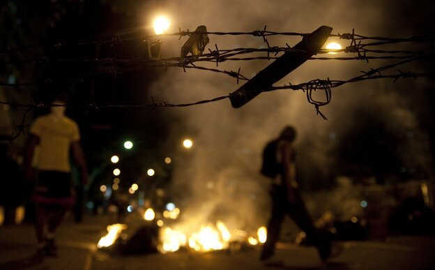 Venezuelan anti-government students light a fire during clashes with riot policemen in Caracas on Thursday.