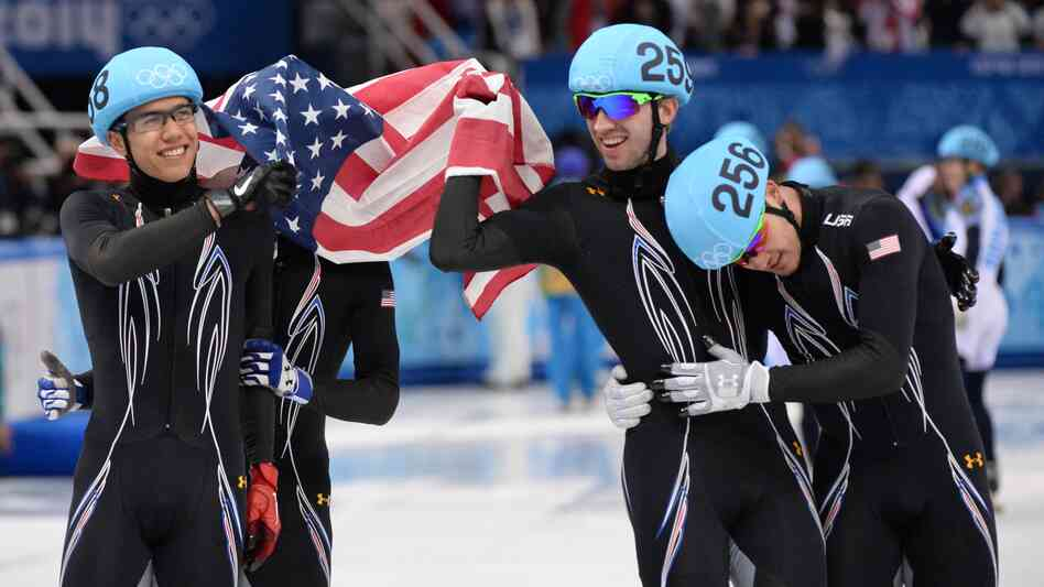 From left to right, America's J.R. Celski, Jordan Malone, Christopher Creveling and Eduardo Alvarez celebrate taking silver in the men's short track 5,000-meter relay at the Iceberg Skating Palace in th
