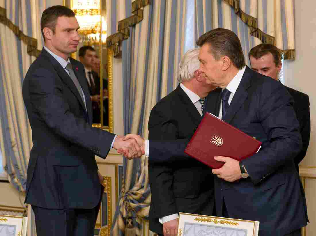 Ukrainian President Viktor Yanukovych (right) and opposition leader Vitali Klitschko shake hands Friday after signing an agreement that diplomats hope will end the