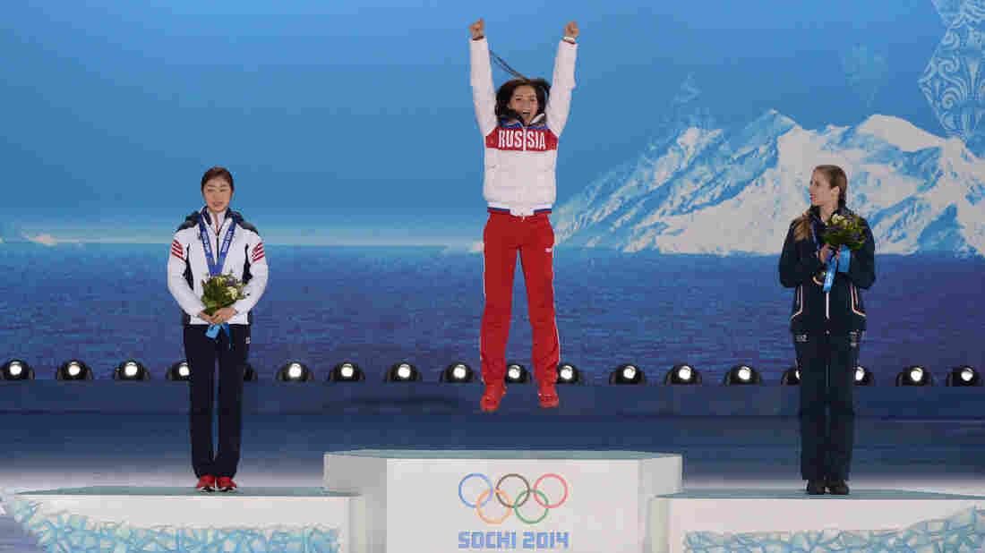 Russia's Adelina Sotnikova (center) celebrates after receiving her gold medal in women's figure skating Thursday. South Korea's Yuna Kim (left) took silver, and Italy's Carolina Kostner won bronze.
