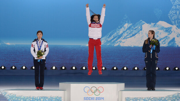 Russia's Adelina Sotnikova (center) celebrates after receiving her gold medal in women's figure skating Thursday. South Korea's Yuna Kim (left) took silver, and Italy's Carolina Kostner won bronze.