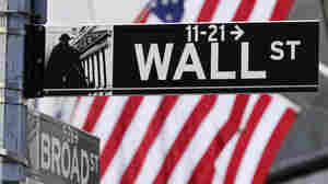 Image #: 21481811 The American Flag can be seen behind a sign for Wall Street near the New York Stock Exchange in New York City on March 5, 2013. UPI/John Angelillo /LANDOV