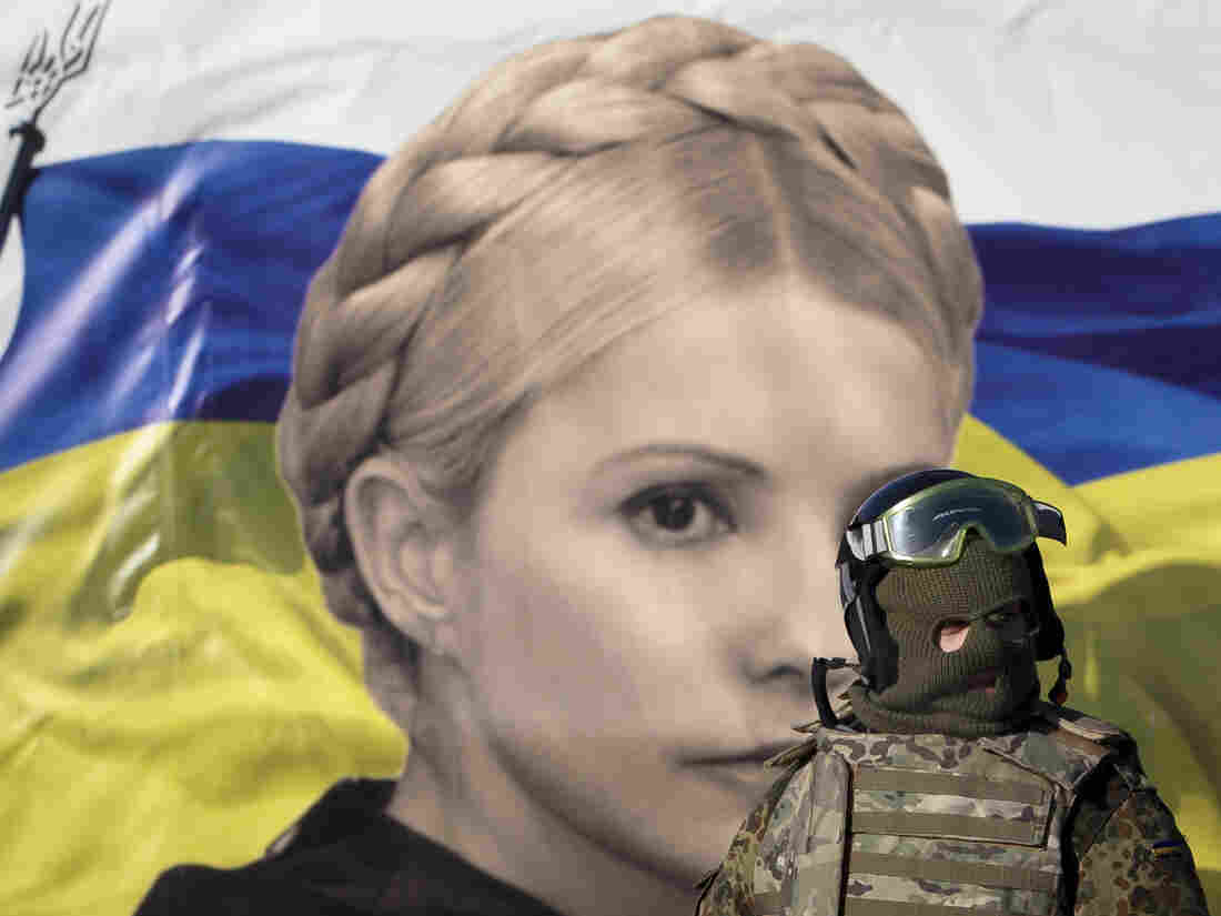 In Kiev last month, this anti-government protester in protective gear stood in front of a poster featuring an image of former Prime Minister Yulia Tymoshenko. Her jailing on what supporters believe were bogus charges was among the complaints protesters raised.