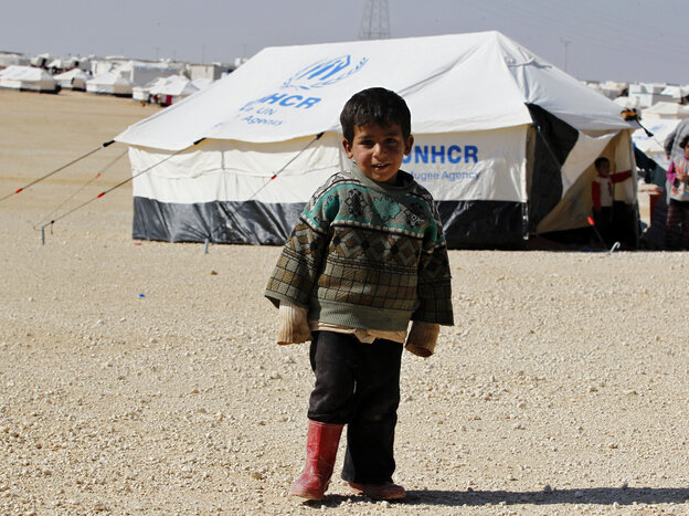 A Syrian refugee boy stands outside his tent at Al Zaatri refugee camp in the Jordanian city of Mafraq
