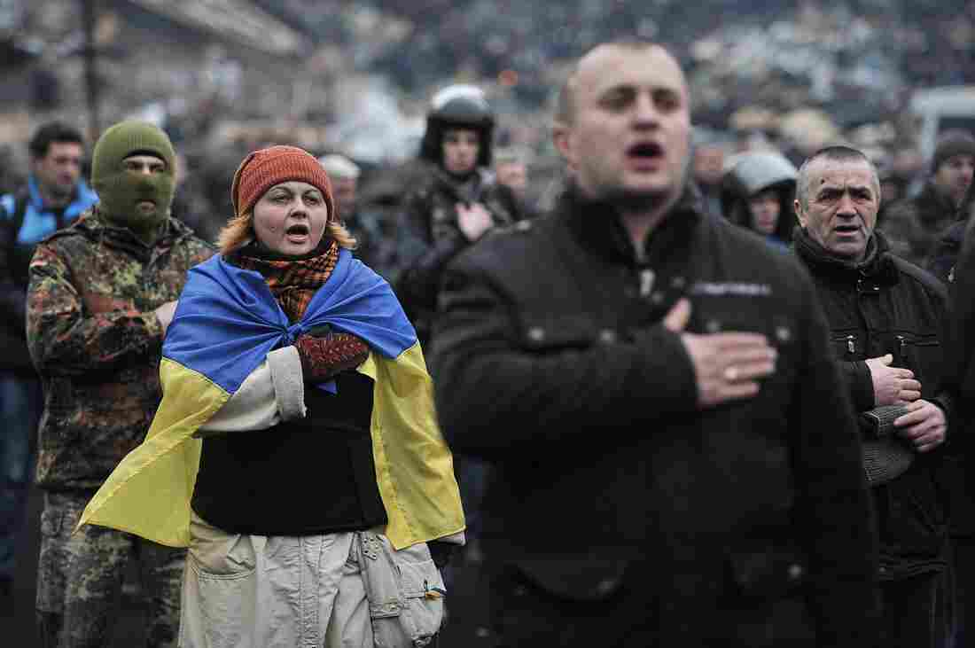 Anti-government protesters sing the Ukrainian national anthem at Independence Square in central Kiev on Saturday.