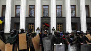Anti-government protesters stand guard in front of Ukraine's parliament in Kiev on Saturday.