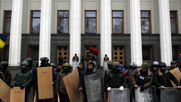 Anti-government protesters stand guard in front of Ukraine's parliament in Kiev on Saturday. (AP)