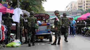 Thai soldiers check the site of a bomb explosion in Bangkok, Thailand, on Sunday. At least 22 people, including three children, were wounded in a bomb explosion near an anti-government protest site.