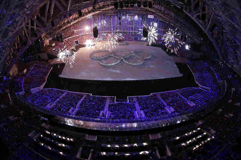 Pyrotechnics explode over dancers formed into the Olympic rings during the closing ceremony of the 2014 Winter Olympics on Sunday.