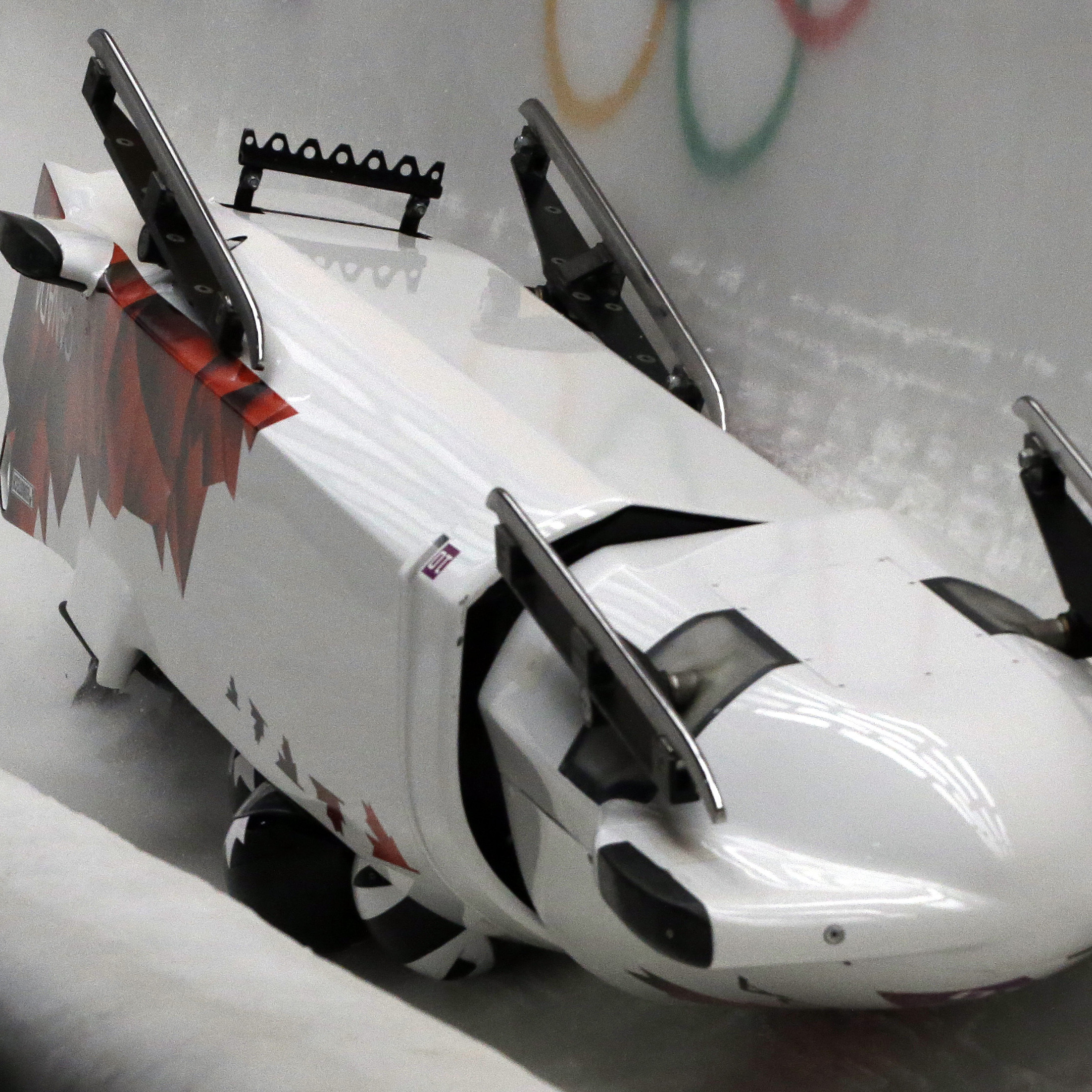 The team from Canada CAN-3, with Justin Kripps, Jesse Lumsden, Cody Sorensen and Ben Coakwell, slide down the track upside down after crashing in turn sixteen during the men's four-man bobsled competition at the 2014 Winter Olympics on Saturday.