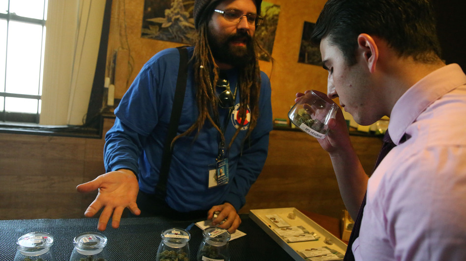 A customer smells a strain of marijuana while being helped by employee Billy Archilla inside the retail marijuana shop at 3D Cannabis Center in Denver. (Brennan Linsley/AP)