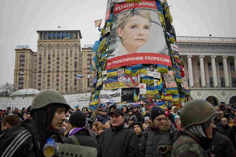 Protesters walk below a poster of Yulia Tymoshenko, in central Kiev, Ukraine on Saturday.
