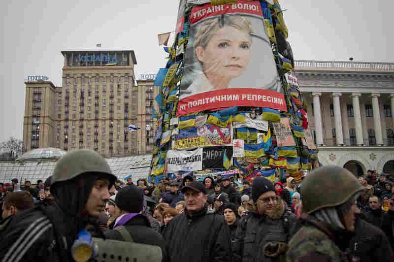 Protesters walk below a poster of Yulia Tymoshenko, in central Kiev, Ukraine on Saturday.