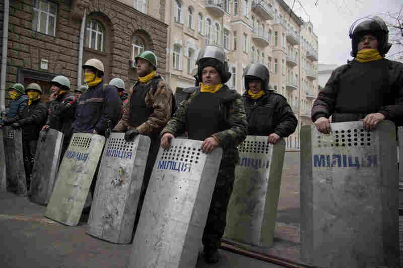 Protesters stand guard in front of presidential administrative building in central Kiev, Ukraine on Saturday. Protesters in the Ukrainian capital claimed full control of the city following the signing of a Western-brokered peace deal aimed at ending the nation's three-month political crisis.