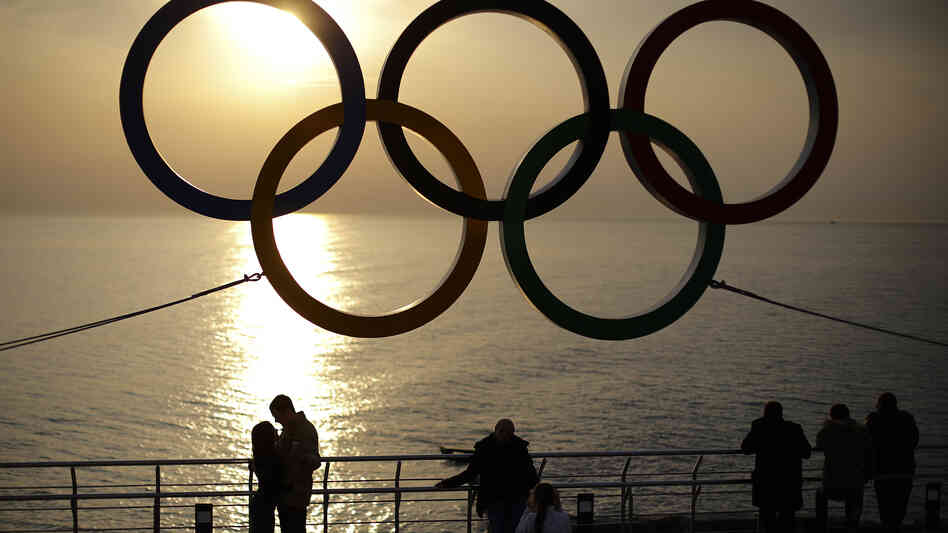 People watch the sunset Monday while standing under the Olympic rings hanging outside a train station in Sochi, Russia.