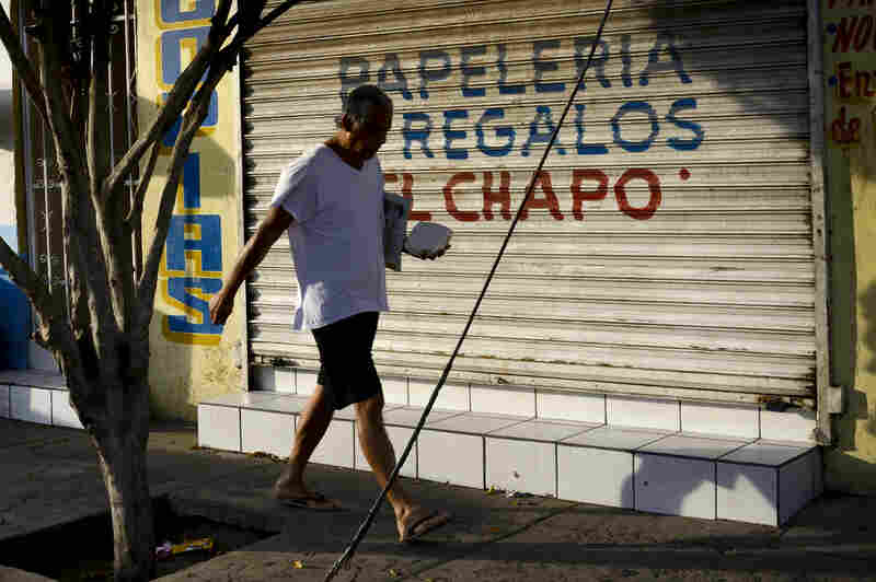 "Mexican marines raided several houses in the working-class neighborhood of La Libertad, from which Joaquin ""El Chapo"" Guzman initially eluded arrest. The morning after the famed drug lord's apprehension, a man walks in front of a store that carries El Chapo's name."