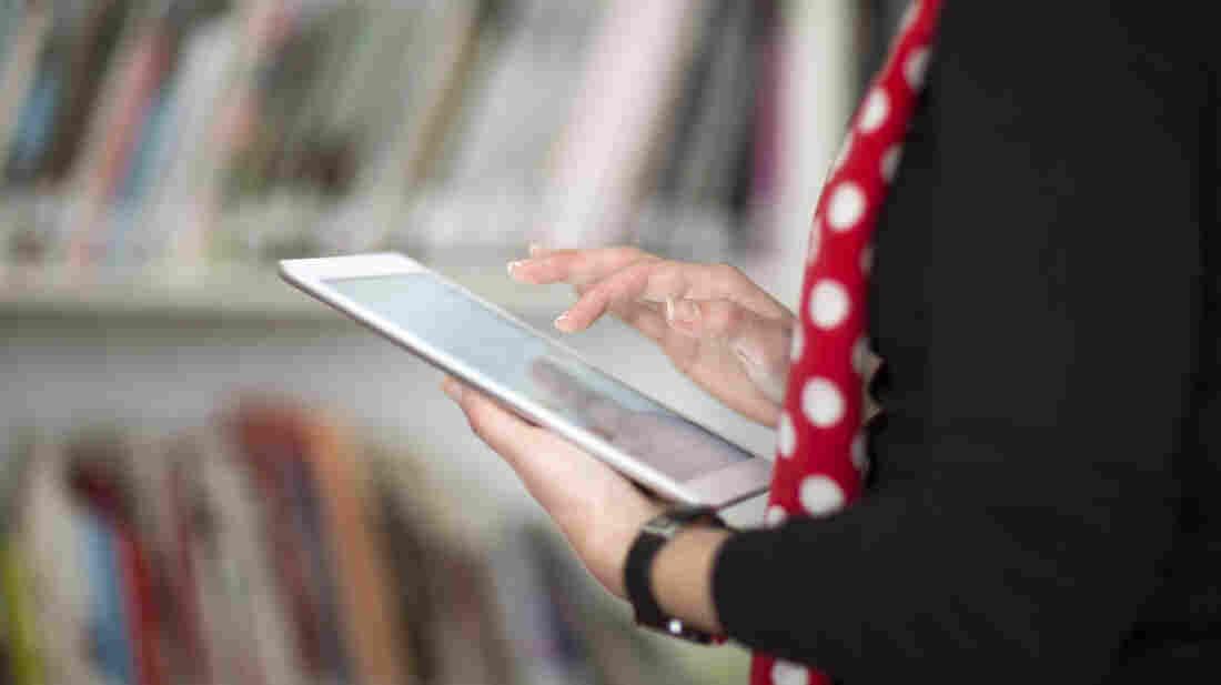 A woman holds an e-book reader.