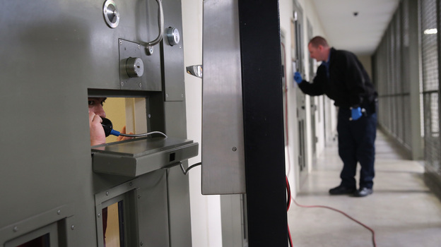 """The U.S. holds more prisoners in solitary confinement than any other democratic country, according to critics of the treatment. Here, an immigrant detainee makes a call from his """"segregation cell"""" at a detention facility in Adelanto, Calif., last November. (Getty Images)"""