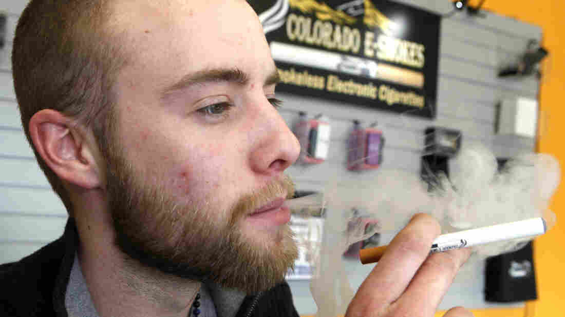 "Blair Roberts, a 22-year-old sales associate at Colorado E-Smokes, ""vapes"" with an electronic cigarette in the Aurora, Colo., store. In the absence of federal rules, Colorado is among states that considered its own age requirements for the nicotine-delivery devices."