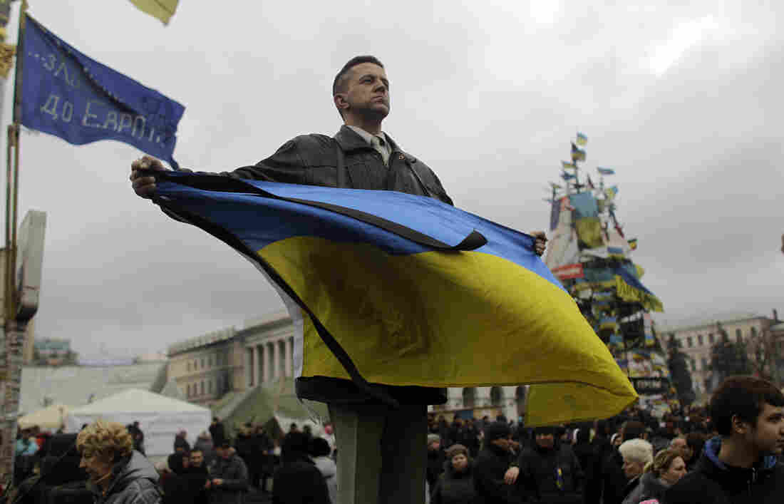 An anti-Yanukovych protester holds a Ukrainian flag in Kiev's Independence Square, the epicenter of the country's current unrest, Tuesday. The Ukrainian Parliament has voted to turn prosecution of ousted President Viktor Yanukovych over to The Hague.