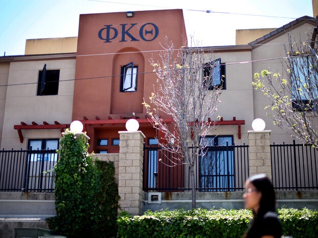 Students walk past the Phi Kappa Theta fraternity house