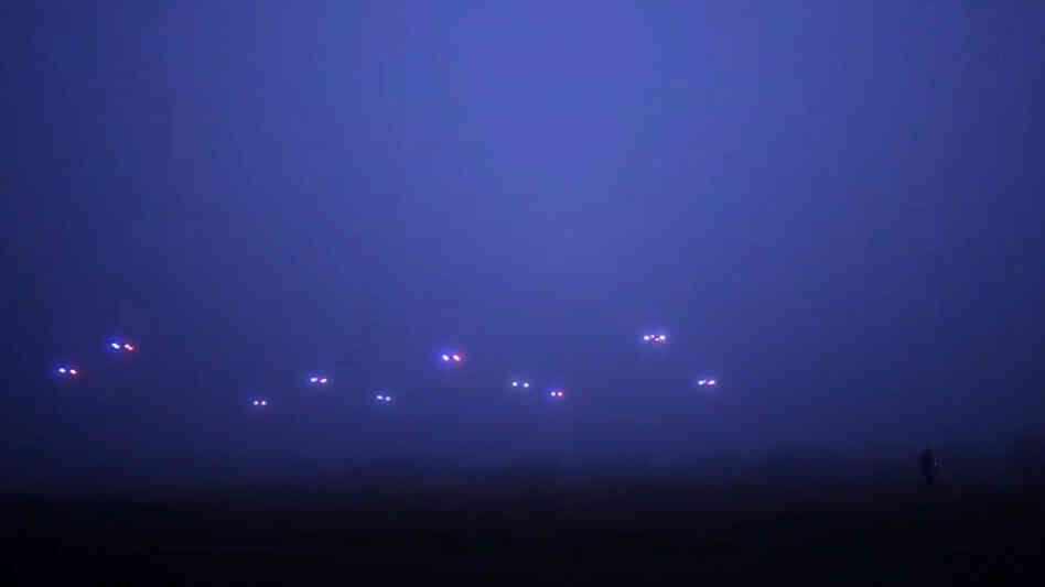 An image from a video by the COLLMOT Robotic Research Project shows a group of drones flying autonomously across a field.