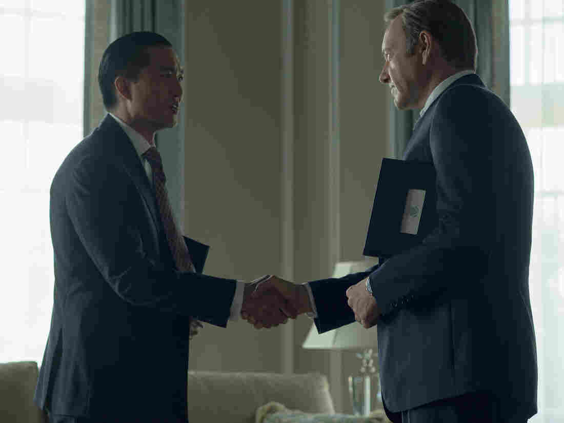 Chinese billionaire Xander Feng, played by Terry Chen, shakes hands with Francis Underwood, played by Kevin Spacey, in Netflix's House of Cards.