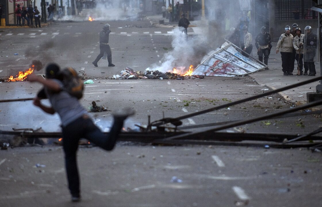 A demonstrator confronts riot policemen during an anti-government protest in Caracas, Venezuela's capital, on Feb. 22.
